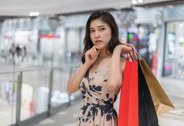 Frau, die einkaufstaschen im mall denkt und hält