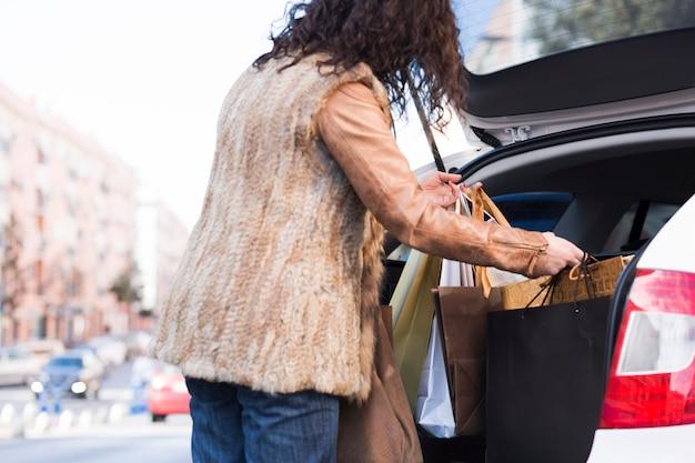 Frau, die einkaufstaschen in auto einsetzt