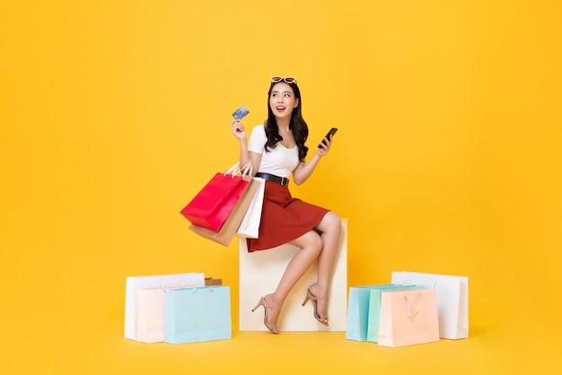 Frau, die einkaufstaschen mit kreditkarte und handy in händen trägt
