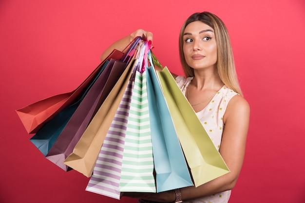 Frau, die einkaufstaschen mit neutralem ausdruck auf roter wand trägt.
