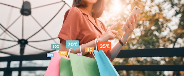 Frau, die einkaufstaschen mit sonderangebot-promo der show-symbolrabatt hält und smartphone auf dem anwendungs-online-shop sucht.