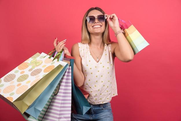 Frau, die einkaufstaschen trägt, während sie ihre brille hält.