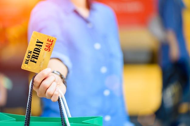 Frau, die einkaufstaschen und kreditkarte im supermarkt hält. black friday-konzept.
