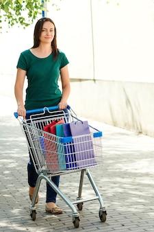 Frau, die einkaufswagen am parkplatz drückt. frau nach dem einkaufen zum auto gehen. großer sommerschlussverkauf. einkaufswagen voller einkäufe.