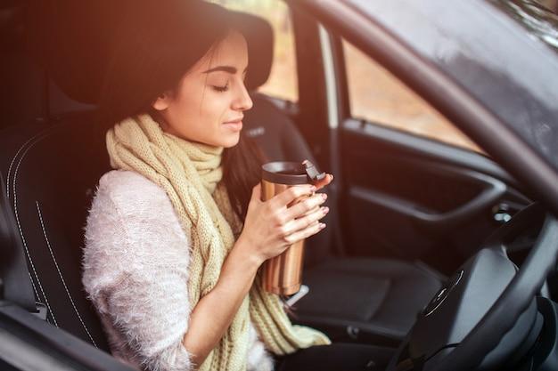 Frau, die einwegtasse kaffee im auto hält