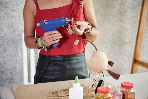 Frau, die elektrische klebepistole für arbeit verwendet