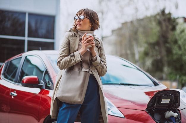 Frau, die elektroauto an der elektrischen tankstelle auflädt und kaffee trinkt
