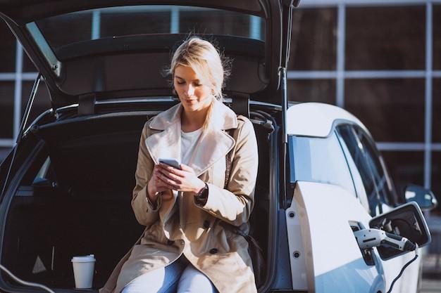 Frau, die elektroauto an der elektrischen tankstelle auflädt