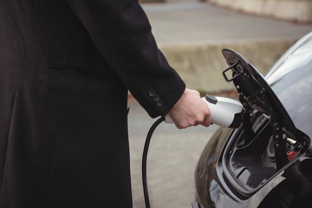 Frau, die elektroauto an der elektrofahrzeugladestation auflädt
