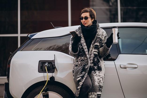 Frau, die elektroauto an der straße auflädt