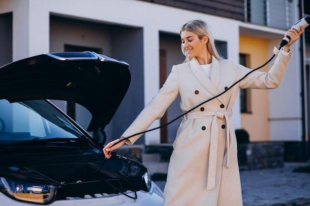 Frau, die elektroauto durch ihr haus auflädt und ladegerät hält