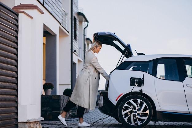 Frau, die elektroauto durch ihr haus auflädt