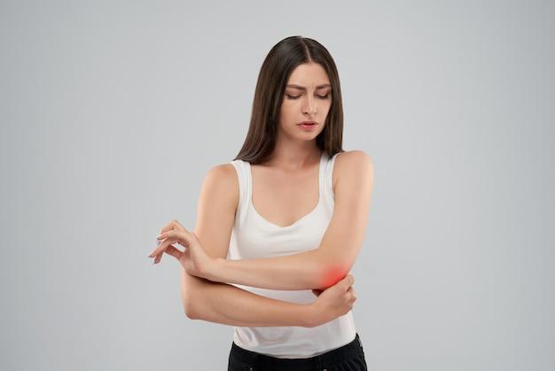 Frau, die ellbogen wegen des schmerzes berührt