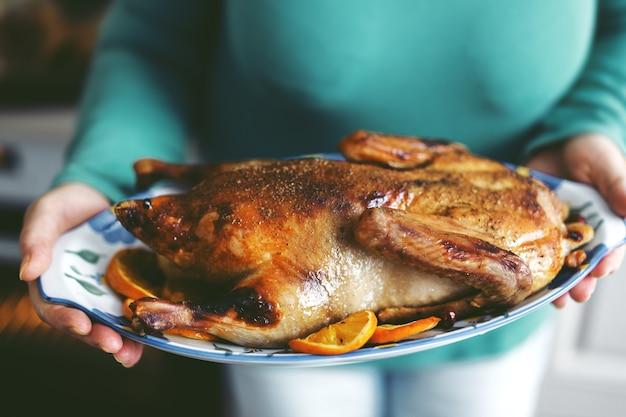 Frau, die ente mit gemüse kocht und es vom ofen setzt. lebensstil. weihnachts- oder erntedankkonzept.