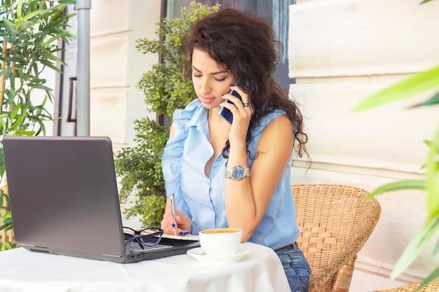 Frau, die entfernt mit laptop und telefon im café arbeitet. glückliche geschäftsfrau, die auf handy anruft und nimmt. schöne brünette mit notizbuch im café. freiberuflich
