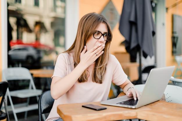 Frau, die entfernt mit laptop und telefon im café arbeitet