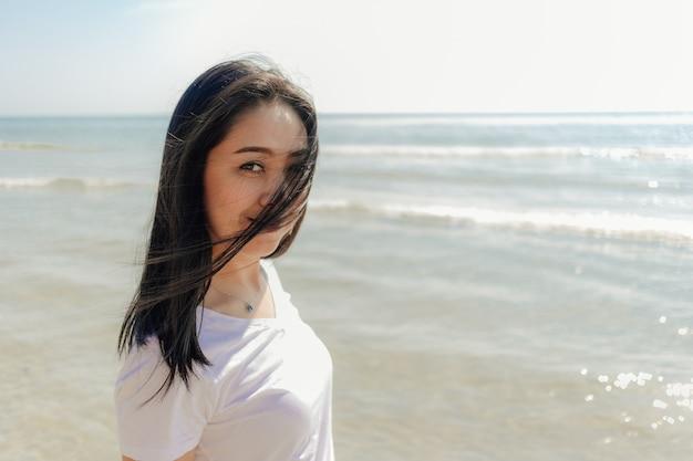 Frau, die entlang den strand unter den sonnigen tag des sommers geht.