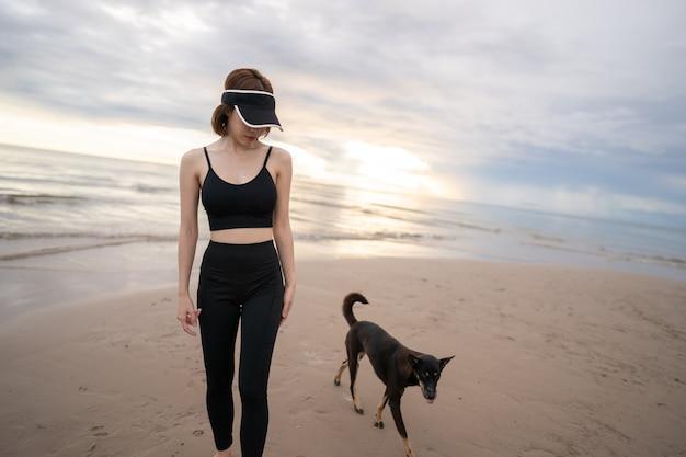 Frau, die entlang eines strandes mit hund am morgen geht