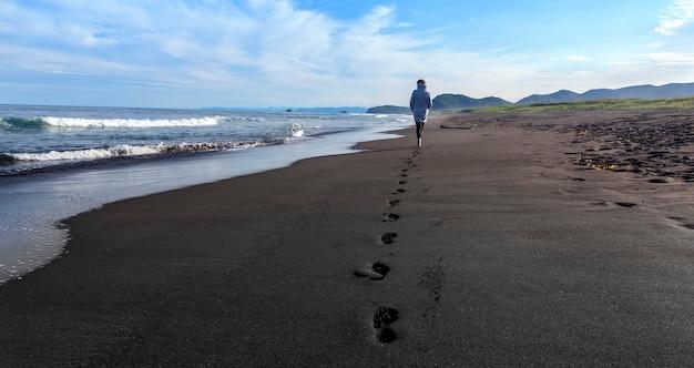 Frau, die entlang schwarzen sandstrand geht