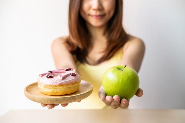 Frau, die entscheidung zwischen gesundem lebensmittel und ungesundem lebensmittel-, gesundem und diätlebensstilkonzept trifft