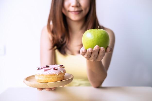 Frau, die entscheidung zwischen gesundem lebensmittel und ungesundem lebensmittel trifft
