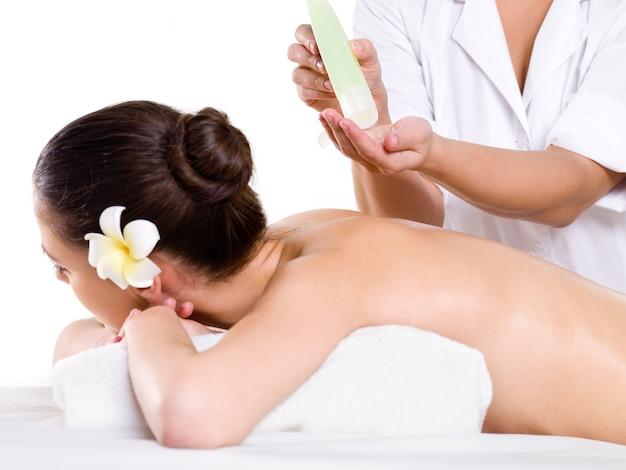 Frau, die entspannende massage im schönheitssalon mit aromatischen ölen hebt