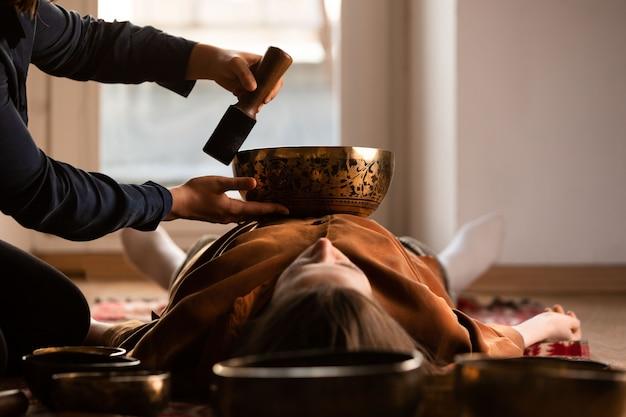 Frau, die entspannende massage, meditation, klangtherapie mit tibetischen klangschalen macht. entspannung