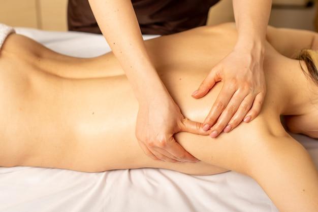 Frau, die entspannende rückenmassage im kosmetik-spa-zentrum genießt