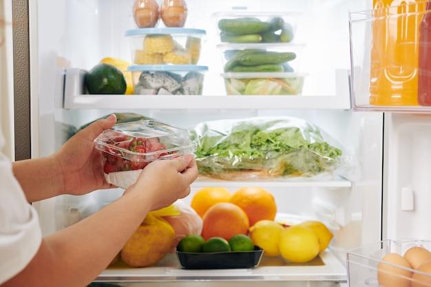 Frau, die erdbeeren in kühlschrank legt