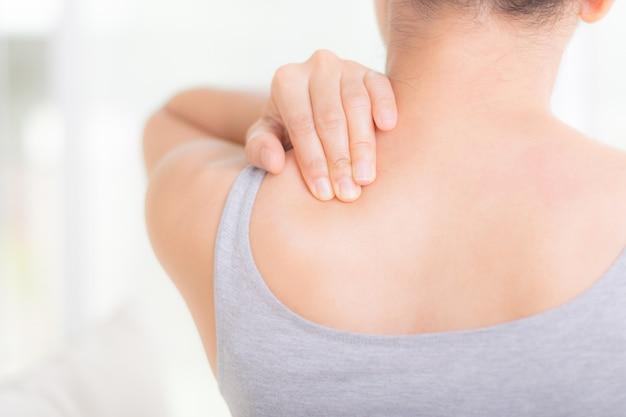 Frau, die erschöpft sich fühlt und unter nacken- und schulterschmerzen leidet.