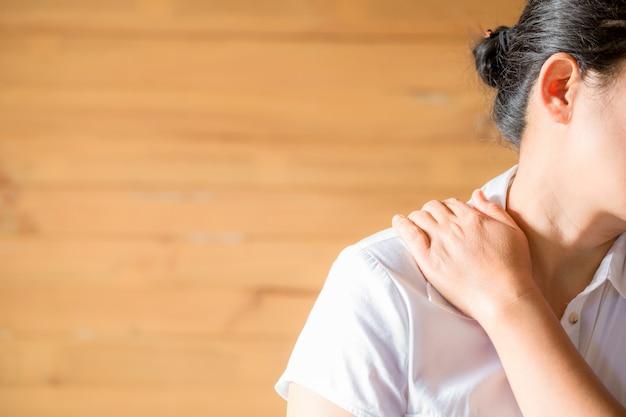 Frau, die erschöpft sich fühlt und unter nackenschmerzen leidet.