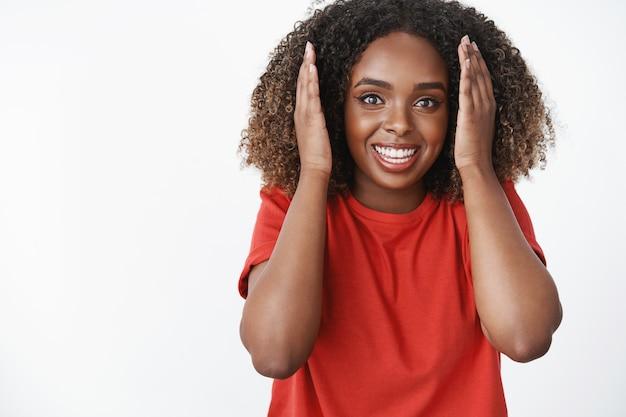 Frau, die erstaunliche und erstaunliche positive nachrichten lernt, die überrascht und amüsiert aussieht, die handflächen in der nähe des gesichts hebt und vor aufregung und glück breit lächelt, die augen beeindruckt vorne