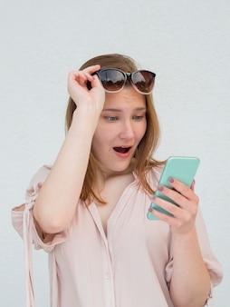 Frau, die erstaunt ist und auf ihrem telefon liest