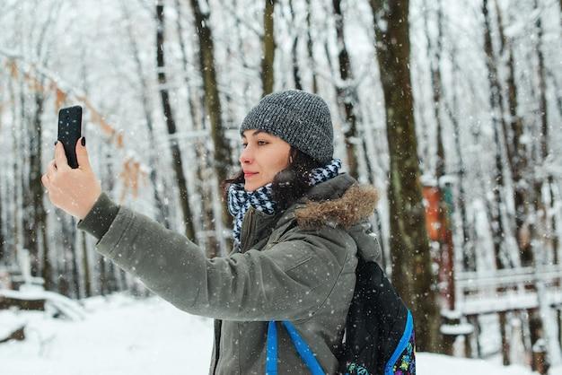 Frau, die ersten schnee genießt. mädchen, das im winterwald geht. frau, die selfie durch smartphone im winter nimmt.