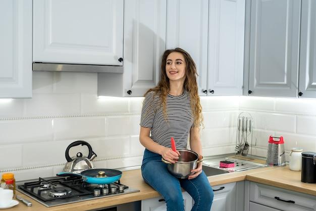 Frau, die essen auf küche mit bratpfanne auf teller kocht