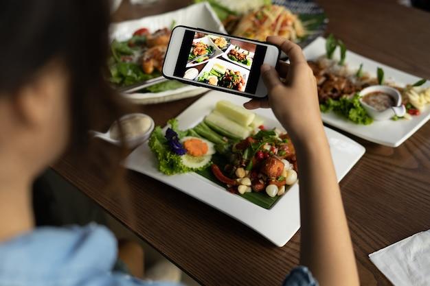 Frau, die essen durch smartphone fotografiert. frau, die fotos von einem köstlichen mittagessen in einem restaurant macht, um in einem sozialen medium hochzuladen.