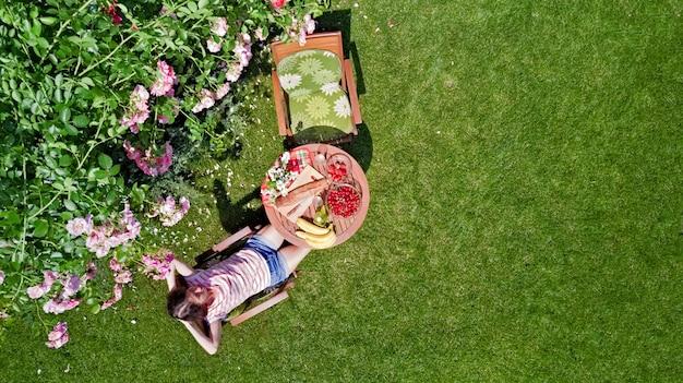 Frau, die essen im schönen rosengarten genießt
