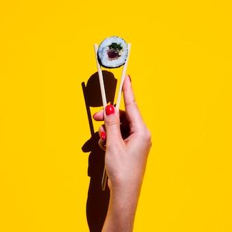 Frau, die essstäbchen mit sushirolle auf gelbem hintergrund hält