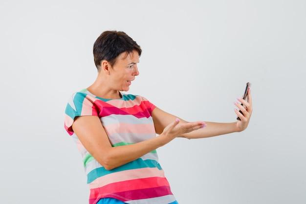 Frau, die etwas auf video-chat im gestreiften t-shirt bespricht und verwirrt aussieht. vorderansicht.