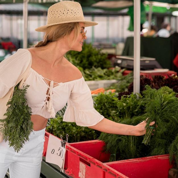 Frau, die etwas dill vom marktplatz nimmt