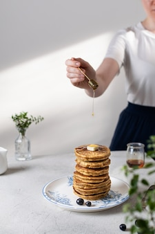 Frau, die etwas honig oder ahornsirup auf stapel pfannkuchen mit blaubeeren und stück butter gießt