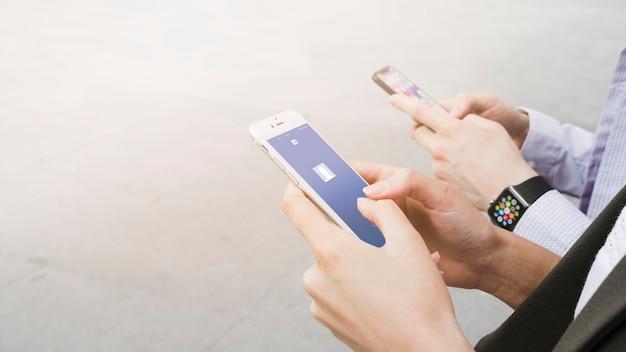 Frau, die facebook-anwendung auf dem beweglichen nahen mann trägt intelligente uhr verwendet