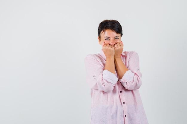 Frau, die fäuste auf gesicht im rosa hemd hält und fröhlich, vorderansicht schaut.