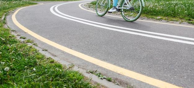 Frau, die fahrrad auf radweg mit markierungen im park fährt