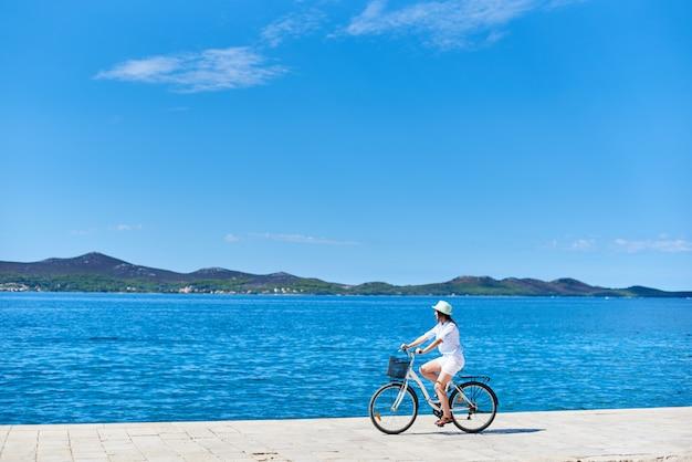 Frau, die fahrrad entlang steinigem bürgersteig auf blaues funkelndes meerwasser fährt