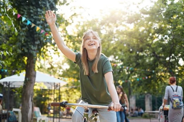 Frau, die fahrrad im park reitet. porträt einer jungen frau, die ein fahrrad im freien im stadtpark a reitet