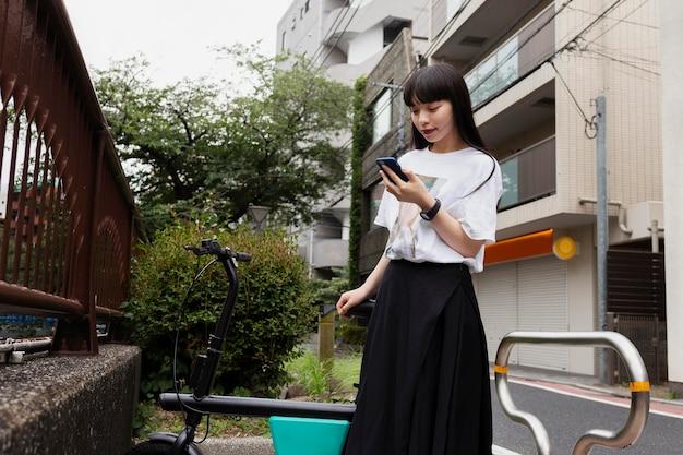 Frau, die fahrrad in der stadt fährt und smartphone betrachtet