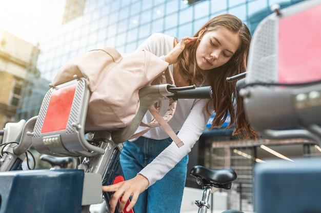 Frau, die fahrrad-teilungsdienst in london city verwendet