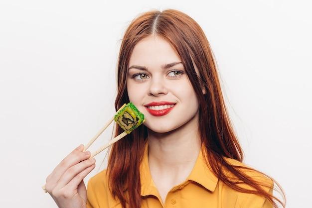 Frau, die farbige brötchen mit bambusstäbchen isst