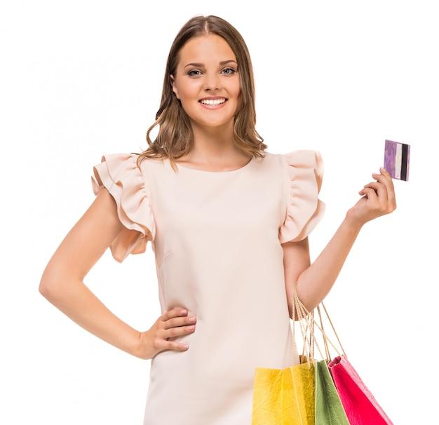 Frau, die farbige einkaufstaschen und kreditkarte hält.